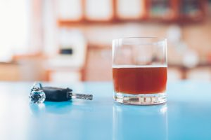 Drink driving. Car key and a glass of liquor on table